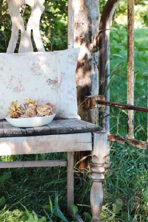Peony and Sage -  French Florals Fabric Collection - A white bowl holding dried flowers beside apink and white floral cushion, on a rustic wooden chair sitting beside a gate