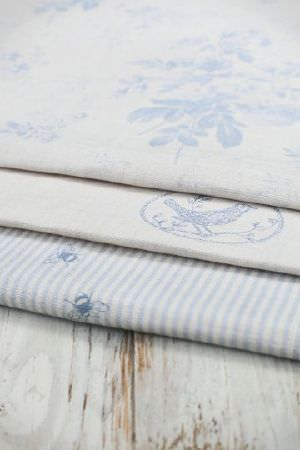 Peony and Sage -  French Florals Fabric Collection - A rustic wooden table with three light blue and off-white fabrics, featuring stripes, bees, circles, birds and florals