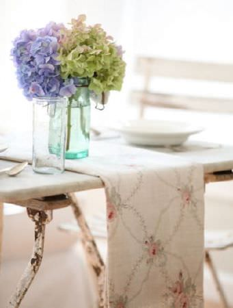 Peony and Sage -  French Florals Fabric Collection - A pale pink, light grey and off-white floral and patterned table runner on a distressed table with a folding chair and vases