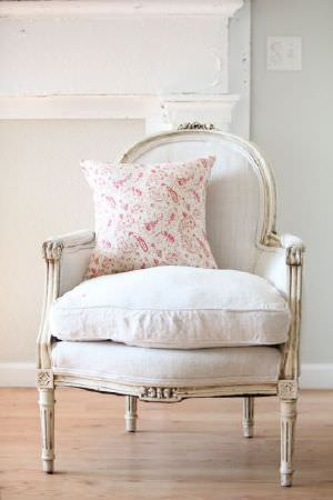 Peony and Sage -  French Florals Fabric Collection - A red and white scatter cushion on an armchair made with a wooden frame and a plainwhite padded seat and back