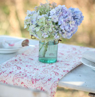 Peony and Sage -  French Florals Fabric Collection - Hydrangeas in a teal glass vase on red and white paisley patterned fabric on a white bench, with napkins and white crockery