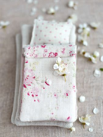 Peony and Sage -  French Florals Fabric Collection - White petals scattered over a tiny bed made with beige mattresses, a pink and beige floral duvet, and a polka dot pillow