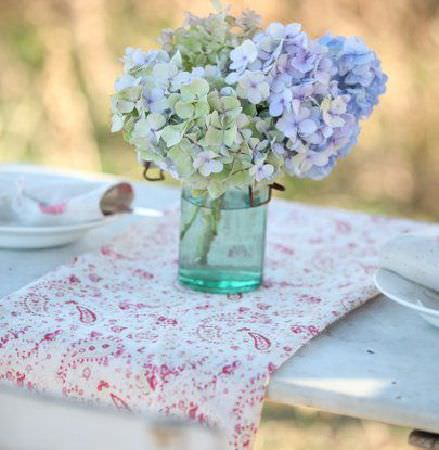 Peony and Sage -  French Florals Fabric Collection - A white bench with white crockery, a fold of red and white paisley patterned fabric, and a turquoise glass vase with flowers