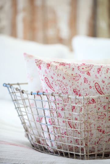 Peony and Sage -  French Florals Fabric Collection - A white wire basket holding two scatter cushions, the front one covered with bright red and white paisley style patterns