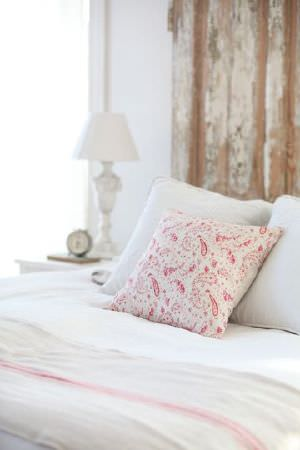 Peony and Sage -  French Florals Fabric Collection - A red and white paisley print cushion with white cushions, on a bed withwhite and pale pink bedding, beside a white lamp