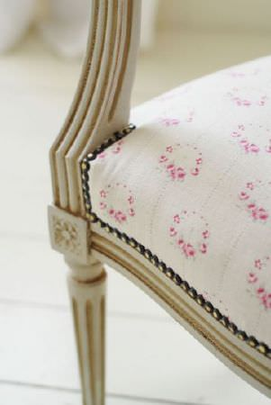 Peony and Sage -  French Florals Fabric Collection - Pretty, delicate, circular floral patterns made in cream and pink covering a padded armchair with a beige wooden frame