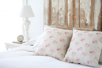 Peony and Sage -  French Florals Fabric Collection - A white lamp beside a bed with a rustic wood headboard, white bedding and two floral scatter cushions in light pink shades