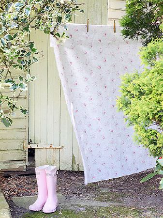Peony and Sage -  French Florals Fabric Collection - Light pink wellies beside pink and white floral patterned fabric hanging on an outdoor washing line, secured by two pegs