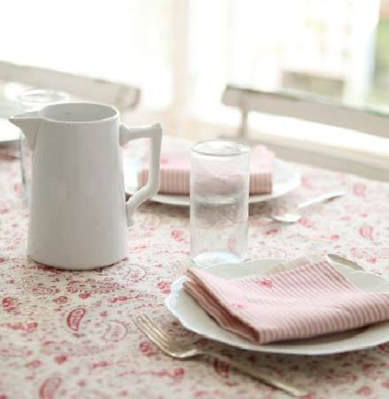 Peony and Sage -  French Florals Fabric Collection - A white jug, plates, cutlery and a glass with striped napkins on a table with a red and white paisley patterned tablecloth