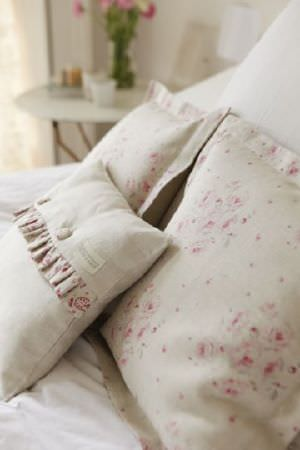 Peony and Sage -  French Florals Fabric Collection - A bed with white bedding and three pale grey scatter cushions, one finished with a frill and two featuring pink florals