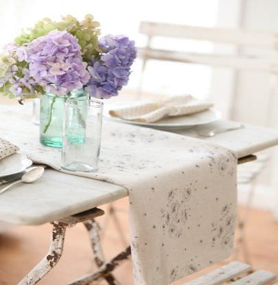 Peony and Sage -  French Florals Fabric Collection - A white table and chairs with a dark grey and white floral table runner, two glass vases holding hydrangeas, and crockery