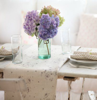 Peony and Sage -  French Florals Fabric Collection - A grey and white floral table runner on a white table with a matching chair, white plates with napkins, 2 glasses and a vase