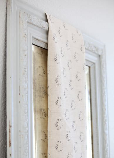Peony and Sage -  French Florals Fabric Collection - A piece of cream coloured fabric featuring a circular dark grey floral pattern, hanging over a white wood framed mirror