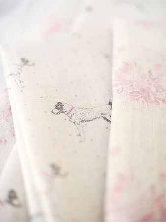 Peony and Sage -  Jack and Jill Fabric Collection - Several folds of beige fabric, some with subtle pale pink florals, some with tiny pink stars and shaded grey dogs