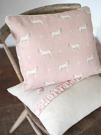 Peony and Sage -  Jack and Jill Fabric Collection - White dogs and stars printed on a pale pink cushion,with a beige cushion with a floral strip and buttons, on a wooden chair