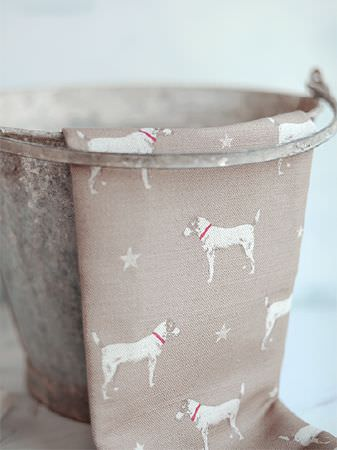 Peony and Sage -  Jack and Jill Fabric Collection - Rusty metal bucket draped with fabric made in light brown with a pattern of rows of stars and dogs with red collars
