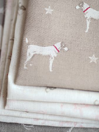 Peony and Sage -  Jack and Jill Fabric Collection - A stack of various cream and grey patterned fabrics, topped with folds of light brown, white and red dog and star print fabric