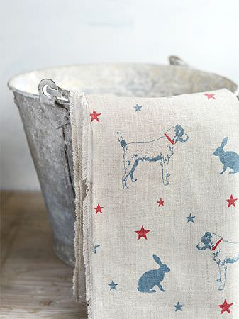 Peony and Sage -  Jack and Jill Fabric Collection - White fabric patterned with blue and red stars, dogs and hares, draped over a rustic white metal bucket