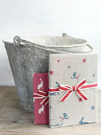 Peony and Sage -  Jack and Jill Fabric Collection - Gifts in red fabric with white hares, and red, grey and blue dog and star print fabric, tied with red ribbon beside a bucket