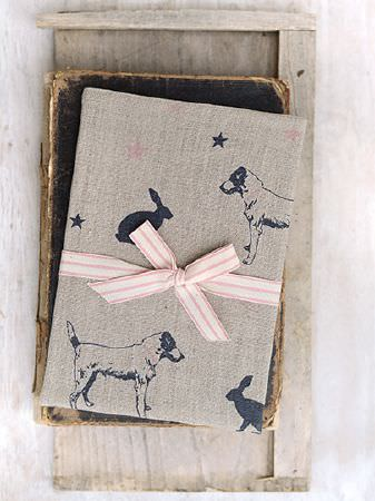 Peony and Sage -  Jack and Jill Fabric Collection - Light grey fabric with navy stars, dogs and hares, tied withwhite and beige ribbon, on a vintage book and wooden boards