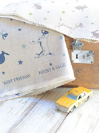 Peony and Sage -  Jack and Jill Fabric Collection - Dog, star and hare print fabrics, one in grey and white, one in grey and navy, on a leather suitcase with a yellow toy car