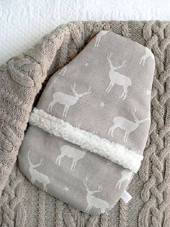 Peony and Sage -  Jack and Jill Fabric Collection - Hot water bottle covered with grey stag and star print fabric with fluffy trim, on a brown knitted blanket and a white rug