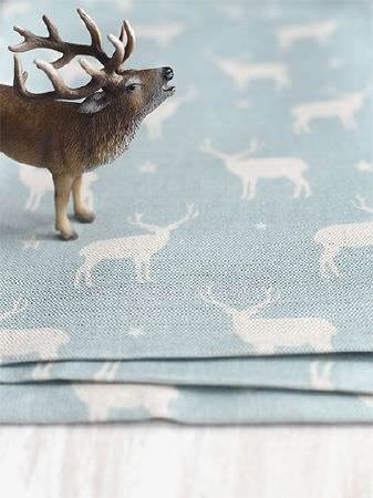 Peony and Sage -  Jack and Jill Fabric Collection - Plastic toy stag standing on 3 pieces of sky blue coloured fabric featuring a repeated white stag and star print design