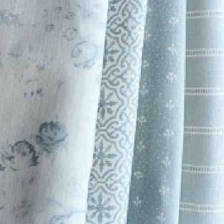 Peony and Sage -  Living Pretty Fabric Collection - Folds of pale blue-grey and whitefabric with small, subtle floral,patterned and striped designs