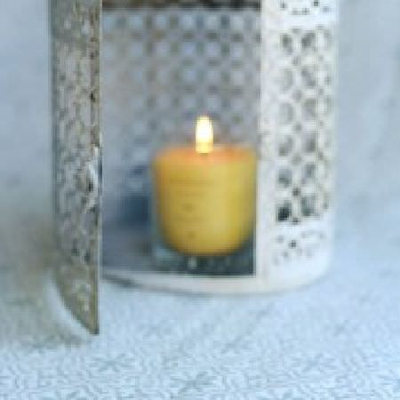Peony and Sage -  Living Pretty Fabric Collection - A yellow candle in a pale grey lantern, sitting on a surface patterned with a small light grey-blue and white design
