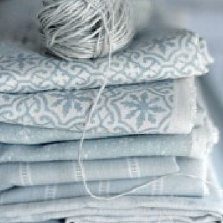 Peony and Sage -  Living Pretty Fabric Collection - A stack of pale blue-grey and white patterned, plain and striped fabrics, topped with a ball of pale blue-grey string