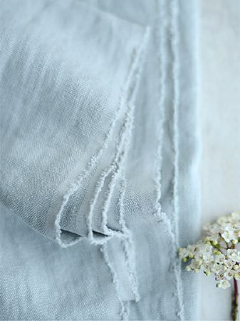 Peony and Sage -  Plain Linens Fabric Collection - Folds of plain light baby blue coloured fabric with a small bunch of tiny white baby