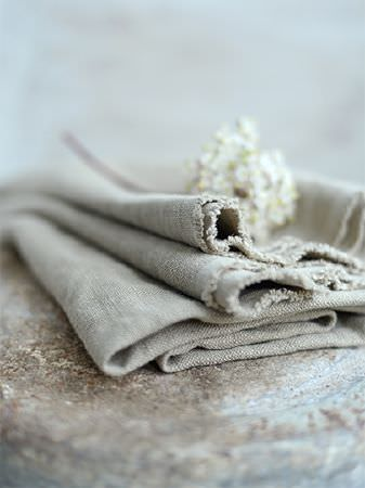 Peony and Sage -  Plain Linens Fabric Collection - Plain light grey fabric folded up and lying on a rustic surface, with a small bunch of tiny white baby