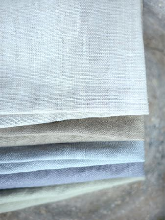 Peony and Sage -  Plain Linens Fabric Collection - A pile of folded fabrics in plain, flat shades of pale grey, light brown, powder blue, denim blue and light green