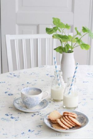 Peony and Sage -  Skandi Range Fabric Collection - A white vase, two milk bottles, a bowl, a teacup and a saucer on a table with ablue and white floral tablecloth