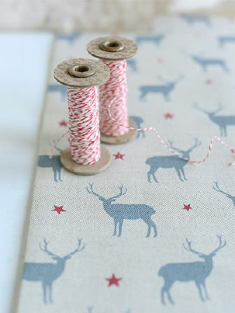 Peony and Sage -  Skandi Range Fabric Collection - Stag and star print fabric made in off-white, red and light blue, placed beneath two spools of red and white thread