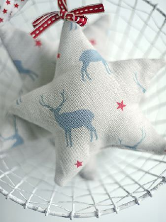 Peony and Sage -  Skandi Range Fabric Collection - A white wire basket holding two fabric stars withwhite, light blue and red stag and star prints, tied with red ribbon