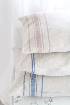 Peony and Sage -  Skandi Range Fabric Collection - A pile of 4 off-white cushions, featuring light grey florals or one of 2 different stripe designs in denim blue or beige