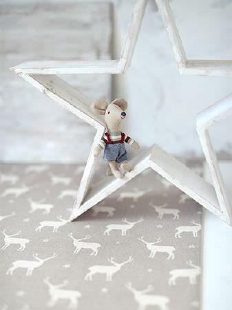 Peony and Sage -  Skandi Range Fabric Collection - A small stuffed toy mouse sitting in a hollow white wooden star, placed ongrey and white stag and star print fabric