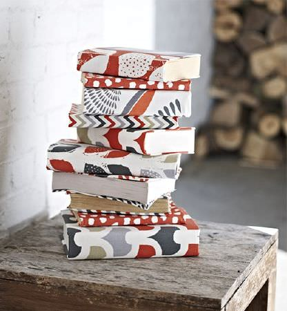 Prestigious Textiles -  Accent Fabric Collection - Stack of ten books on a rustic wooden table, each book covered in a patterned fabric featuring red, white, grey, green and black colours