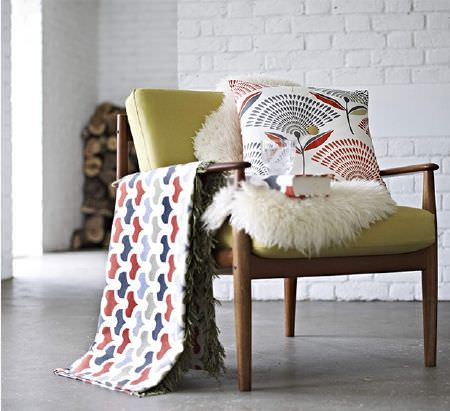 Prestigious Textiles -  Accent Fabric Collection - Armchair with thin wooden frame, lime green seat cushions, a sheepskin, and patterned fabrics made into a blanket, cushion and book cover