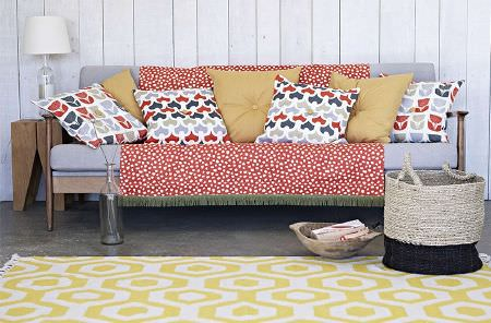 Prestigious Textiles -  Accent Fabric Collection - Yellow and white geometric print rug, with a blue, wooden-framed sofa, plain and patterned cushions, a wooden table, white lamp and basket