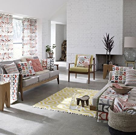 Prestigious Textiles -  Accent Fabric Collection - Co-ordinating cushions, blankets and curtains in a variety of patterns, with a patterned rug, blue sofas, a green armchair, lamps and tables