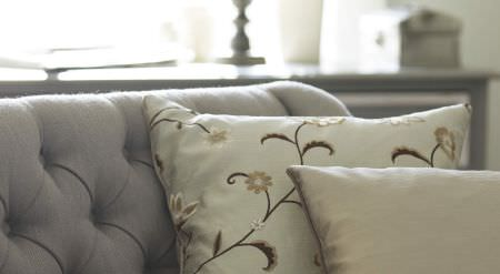 Prestigious Textiles -  Amour Fabric Collection - A modern room with floral brown and white cushions