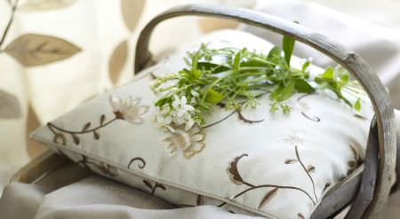 Prestigious Textiles -  Amour Fabric Collection - A white and brown floral cushion with fresh flowers