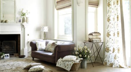 Prestigious Textiles -  Amour Fabric Collection - A well furnished room with cushions, curtains and roman blinds in shades of white, yellow and brown
