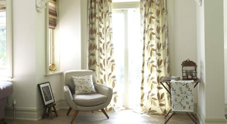 Prestigious Textiles -  Amour Fabric Collection - A well furnished room with cushions, curtains, roman blinds and a throw in shades of white, yellow and brown
