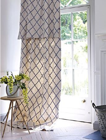 Prestigious Textiles -  Andiamo Fabric Collection - Very long cream and navy blue curtains with a repeated pattern, with a three-legged wooden table, vase and metal bucket