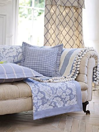 Prestigious Textiles -  Andiamo Fabric Collection - Light blue and cream checked and striped cushions, floral and striped throws with pompoms, curtains, with a beige sofa