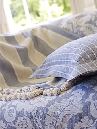 Prestigious Textiles -  Andiamo Fabric Collection - A blue and white checked cushion on throws with florals in light shades of blue, and blue and cream stripes edged with pompoms
