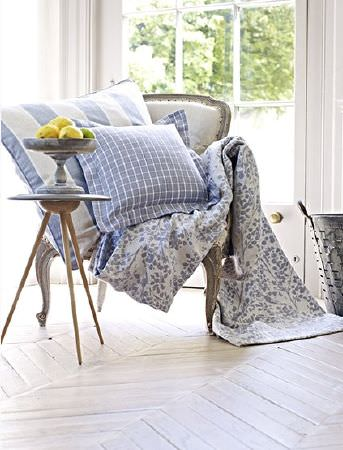 Prestigious Textiles -  Andiamo Fabric Collection - White armchair with a grey wood frame, a blue and white floral throw and patterned cushions, a tripod table and a vase
